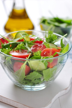 fresh salad with tomatoes cherry, arugula and cucumber in glass bowl photo