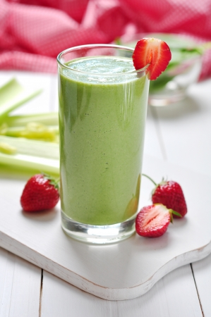 Green vegetable smoothie with celery and strawberry on wooden background photo