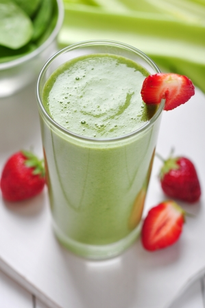 strawberry smoothie: Green vegetable smoothie with celery and strawberry on wooden background