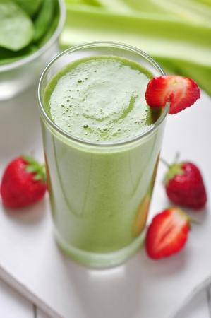 licuados de frutas: Smoothie vegetal verde con apio y fresas en el fondo de madera