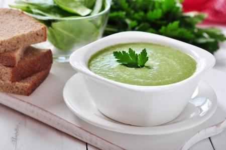 espinaca: sopa de espinacas en un recipiente sobre un fondo de madera