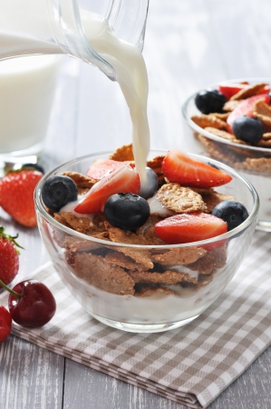Glass bowl with healthy muesli and fresh berries on a wooden background photo