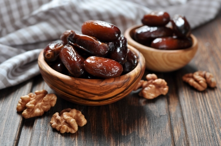 Dates fruit in a wooden bowl closeup on wooden background Stock Photo
