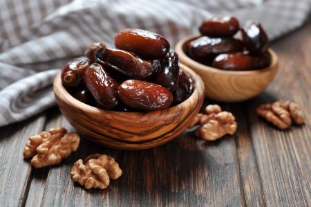 dattes: Dates fruits dans un gros bol en bois sur fond de bois
