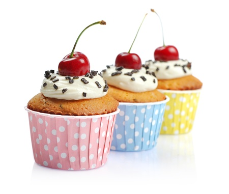 Cupcakes with whipped cream and cherry isolated on white background photo