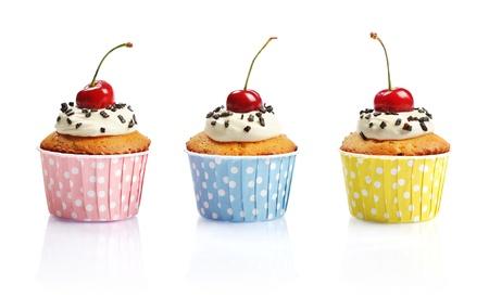 pasteles de cumpleaños: Magdalenas con crema batida y una cereza aisladas sobre fondo blanco