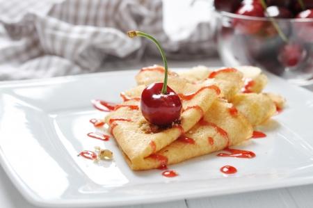 Sweet pancake with cherry sauce and cherries photo