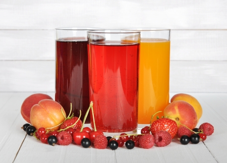 Berry juice in glasses with fresh berries on wooden background photo