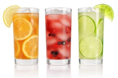 Sommer Getränke mit Eis, frische Beeren, Zitrone und Limette isoliert auf weiß