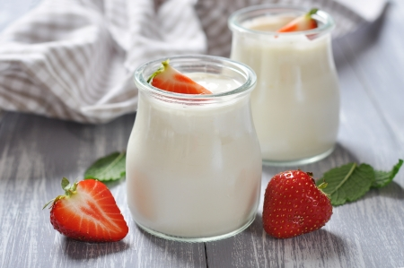 yogurt with ripe fresh strawberry in jars on wooden background photo