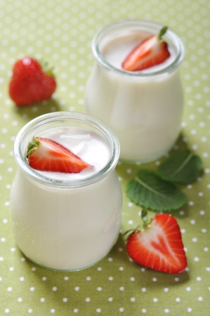 Sour cream: yogurt with ripe fresh strawberry in jars on green background
