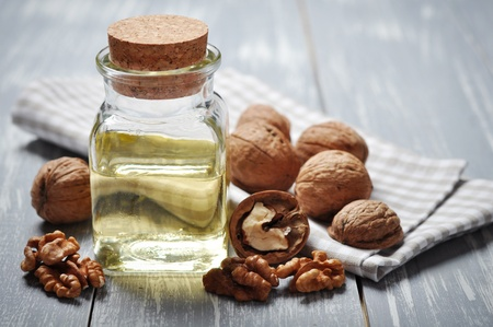 calorie: Walnut oil with nuts on a wooden background