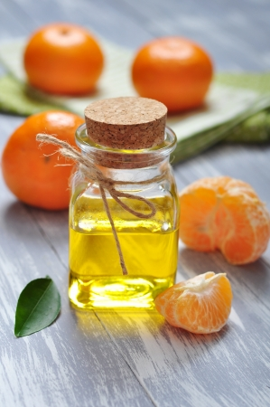 tangerine oil in a glass bottle with fresh tangerine on wooden background photo