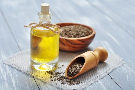 cumin: cumin oil in a glass bottle with cumin seeds on wooden background