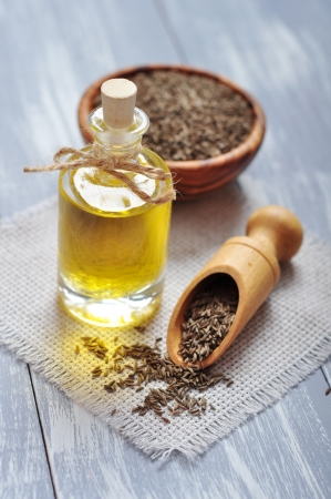 cumin oil in a glass bottle with cumin seeds on wooden background photo