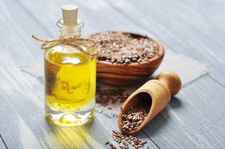 linseed: Linseed oil and flax seeds on wooden background