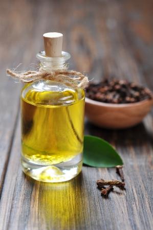 olio corpo: Olio di chiodi di garofano in una bottiglia di vetro su sfondo in legno