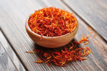 intense flavor: Saffron in wooden bowl on wooden background Stock Photo