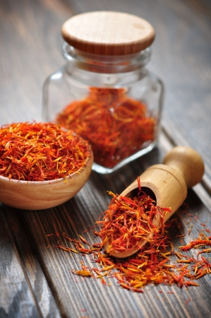 saffron: Saffron in wooden bowl on wooden background Stock Photo