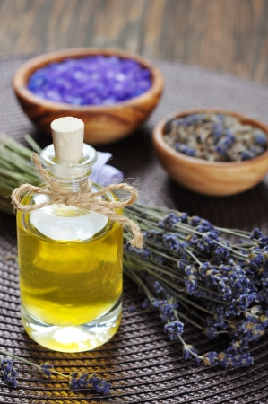essential lavender oil with fresh flowers on wooden background photo