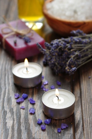candles, herbal soap with oil, sea salt and lavander flowers on wooden background photo