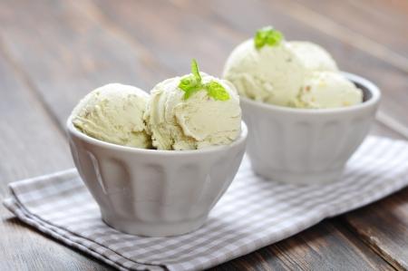 Vanille-ijs met munt in keramische kom op houten achtergrond