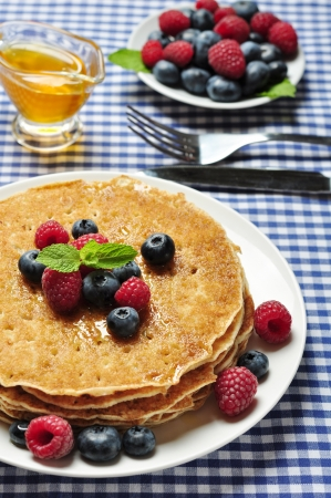Delicious pancakes close up, with fresh blueberries, raspberry and maple syrup pancakes with fresh berries photo