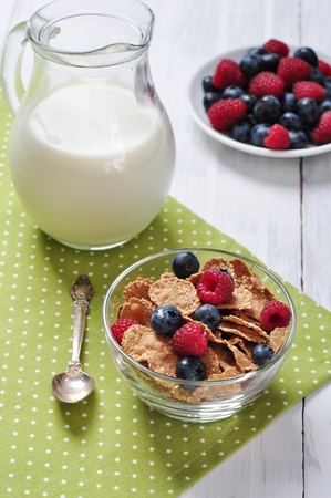 bowl of cereal: cereal flakes with raspberry and blueberry in glass bowl Stock Photo