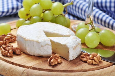 Camembert on wooden cutting board with grape and walnut closeup Stock fotó