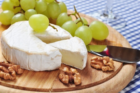 Camembert on wooden cutting board with grape and walnut closeup photo