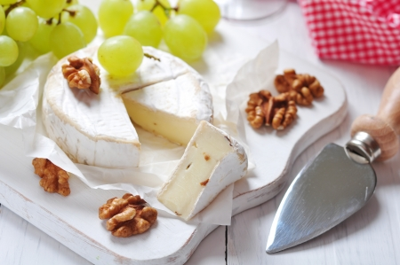 rind: Camembert on wooden cutting board with grape and walnut closeup Stock Photo
