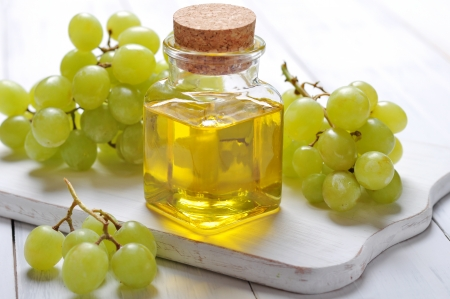 Grape seed oil in a glass jar on wooden background photo