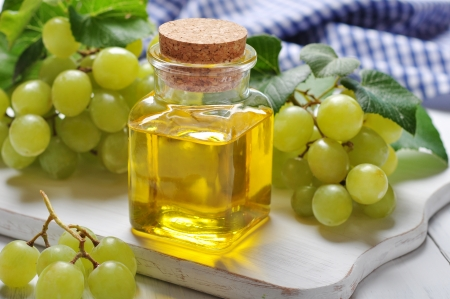 Grape seed oil in a glass jar on wooden background