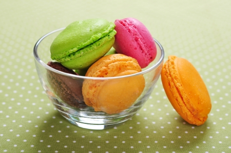 Colorful macaroons in glass bowl over green background photo