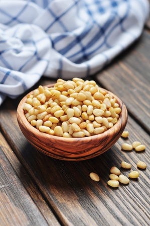 pine nuts: pine nuts in wooden bowl on wooden background