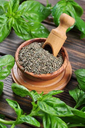 Dry basil in wooden bowl and fresh basil on wooden background photo