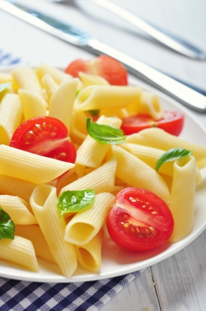 Penne pasta with cherry tomatoes and basil closeup Stock Photo - 21593953