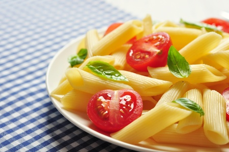 Penne pasta with cherry tomatoes and basil closeup Stock Photo - 21593961