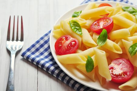 Penne pasta with cherry tomatoes and basil closeup Stock Photo - 21593963