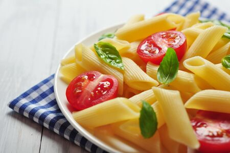 Penne pasta with cherry tomatoes and basil closeup Stock Photo - 21593964