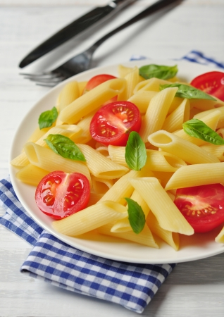 Penne pasta with cherry tomatoes and basil closeup Stock Photo - 21592625