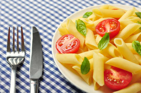 Penne pasta with cherry tomatoes and basil closeup photo