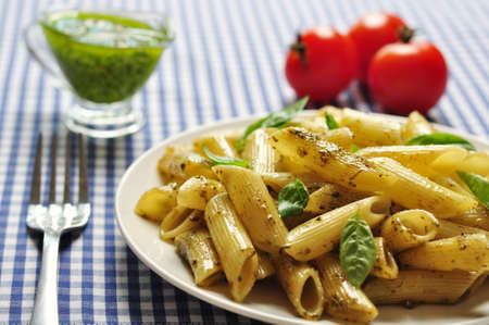 Penne pasta with pesto sauce and basil on white plate Stock Photo - 21593973