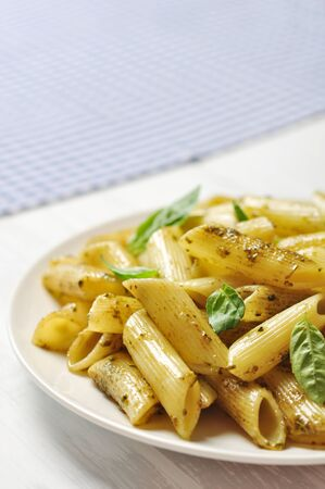 Penne pasta with pesto sauce and basil on white plate Stock Photo - 21592620