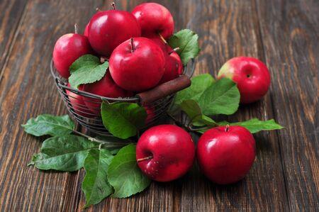 freshly picked: Apples in metal basket on wooden background