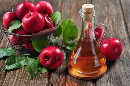 manzana: El vinagre de manzana en botella de vidrio y la canasta con manzanas frescas