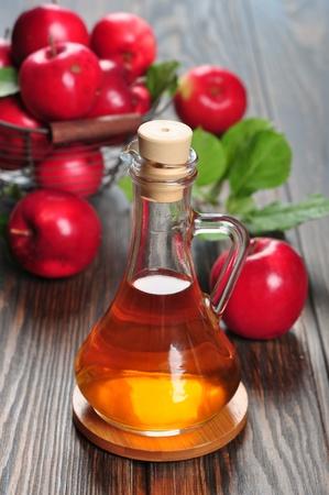 El vinagre de manzana en botella de vidrio y la canasta con manzanas frescas