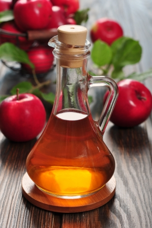 Apple cider vinegar in glass bottle and basket with fresh apples   Stock Photo