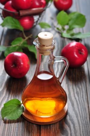 vinegar bottle: Apple cider vinegar in glass bottle and basket with fresh apples