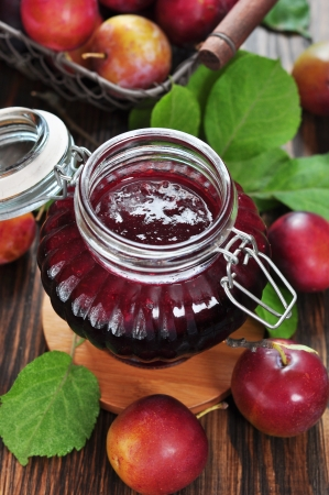Plum jam in a glass jar and fresh fruits with leaves on wooden background closeup photo